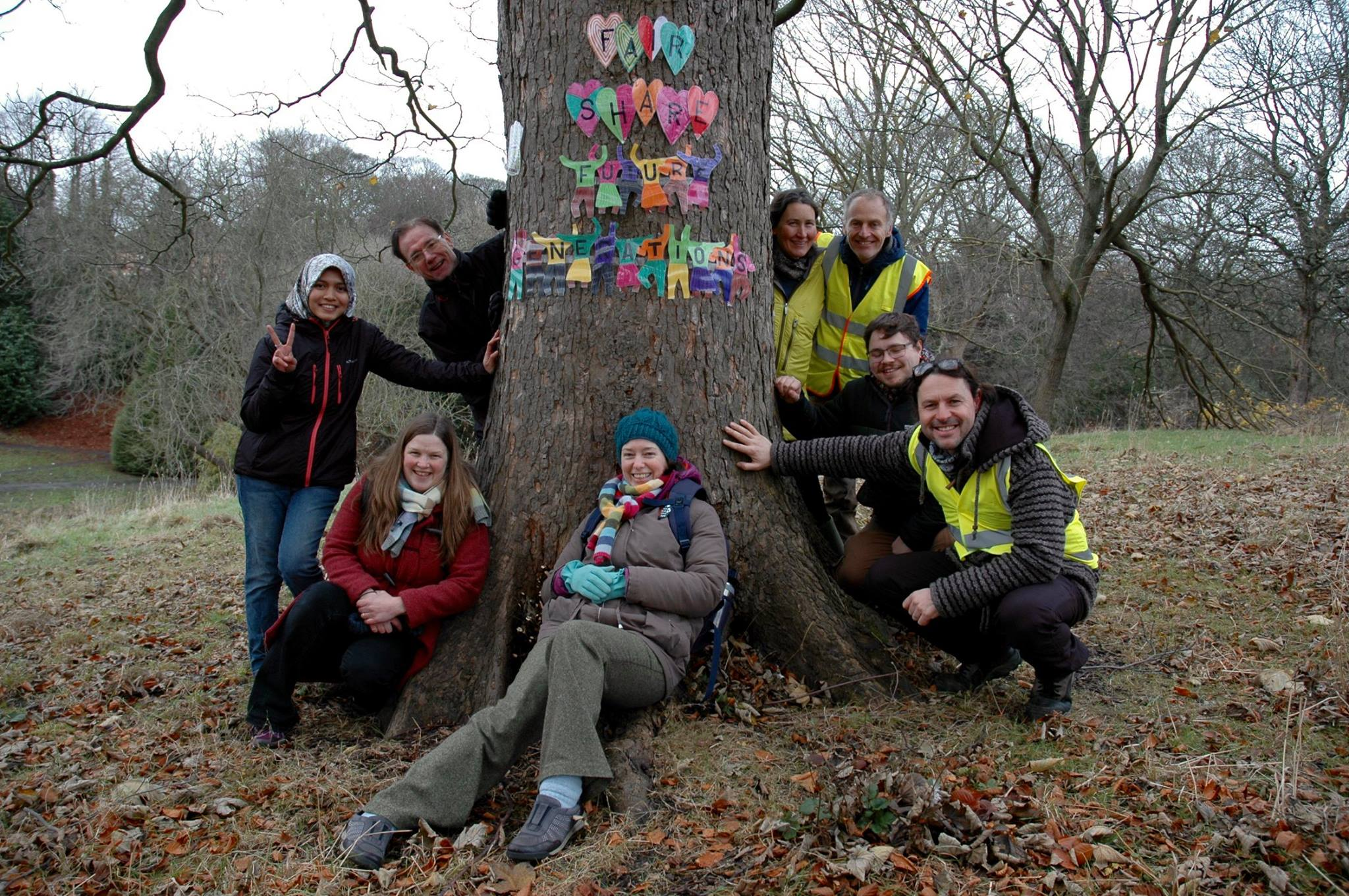 People sitting and leaning against a tree decorated with bunting for National Tree Week