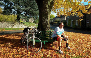 Cyclist resting beneath a village tree with his bike