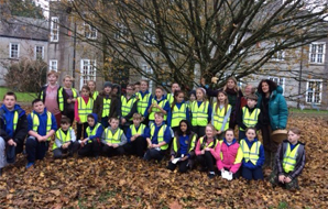 School group in high vis jackets being photographed beneath a tree